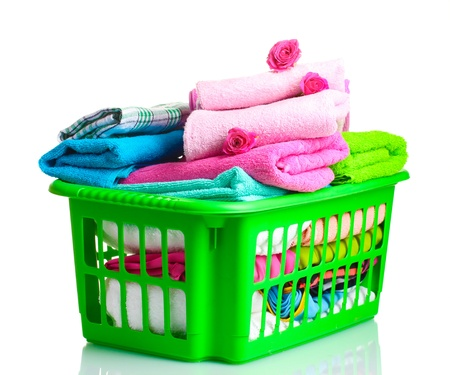 Towels in green plastic basket isolated on white