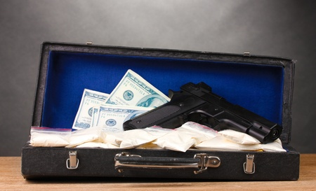 Cocaine, dollars and handgun in case on wooden table on grey background