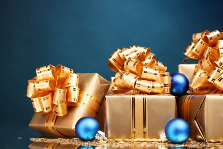 Beautiful gifts in gold packaging and Christmas balls on blue background