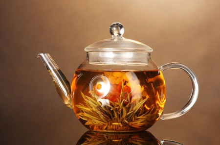 glass teapot with exotic green tea on wooden table on brown background