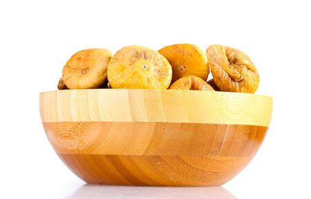 delicious dried figs in wooden bowl isolated on white