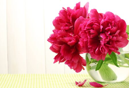 Photo for beautiful pink peonies in glass vase on table on white wooden background - Royalty Free Image