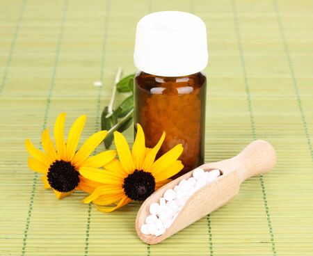 medicine bottle with tablets and flowers on bamboo mat