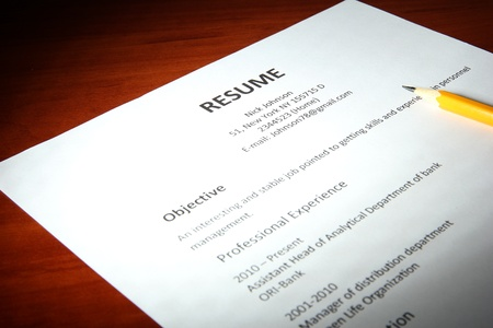 Closeup of resume with pencil on wooden table