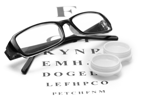 Photo pour glasses and contact lenses in containers, on snellen eye chart background - image libre de droit