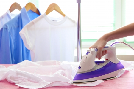 Woman hand ironing a shirt, on cloth background