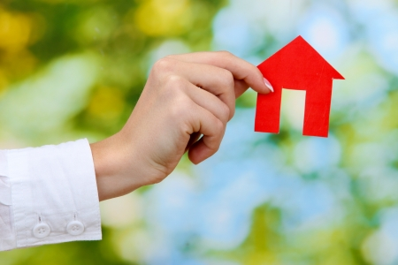 concept: woman hand with paper house on green background, close up