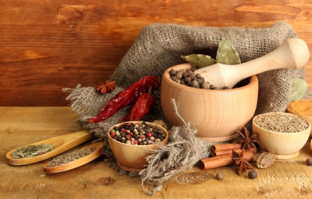 Photo pour mortar, bowls and spoons with spices, on wooden background - image libre de droit
