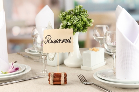 Reserved sign on restaurant table with empty dishes and glasses