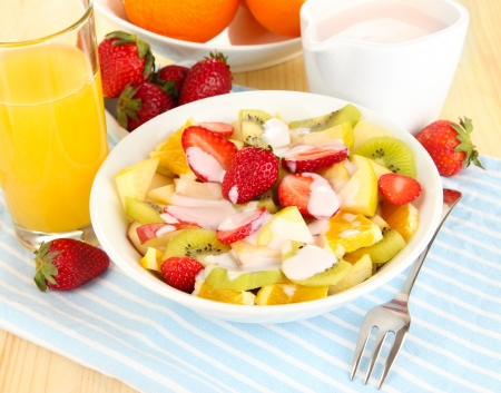 Useful fruit salad of fresh fruits and berries in bowl on napkin on wooden table close-up