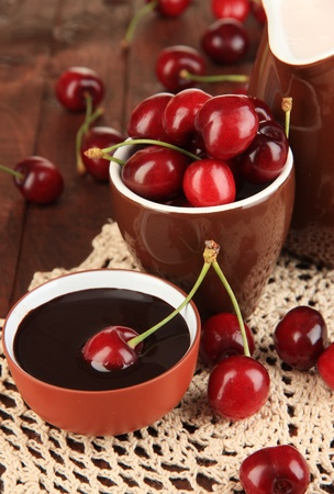 Ripe red cherry berries in cup and chocolate sauce on wooden table close-up