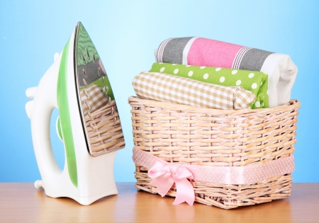 Steam iron and wicker basket with clothes, on color background