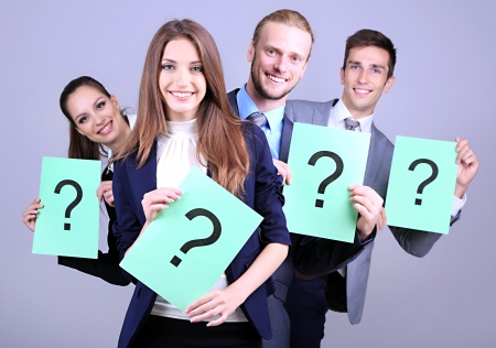 Business team standing in row with question mark on grey background