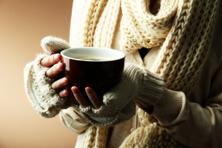 Female hands with hot drink, on color
