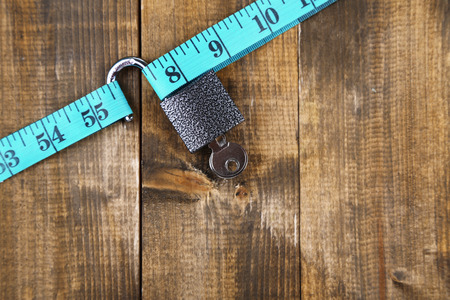 Conceptual photo of unlocking  secret of weight loss. On color wooden background