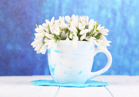 Beautiful snowdrops in vase, on wooden table on bright background