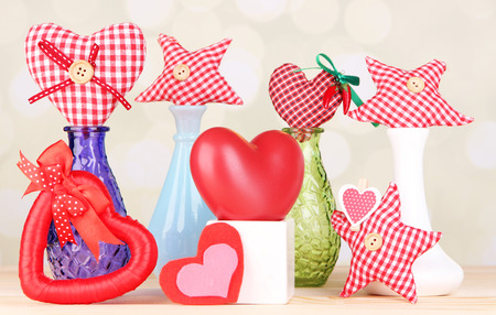 Hand-made textile hearts in different vases on wooden table, on light background