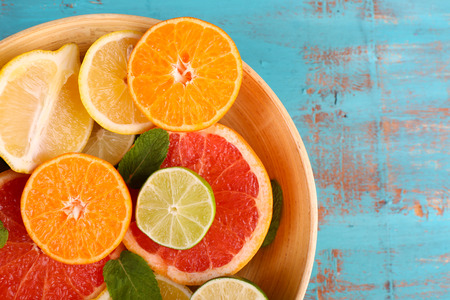 Different sliced juicy citrus fruits in bowl on blue wooden table