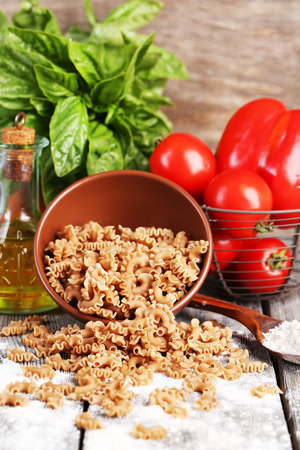Composition of colorful buckwheat pasta in bowl, fresh tomatoes on  wooden background