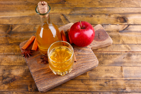 Apple cider in glass bottle with cinnamon sticks and fresh apples on cutting board, on wooden backgroundの写真素材