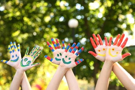 Foto de Smiling colorful hands on natural background - Imagen libre de derechos
