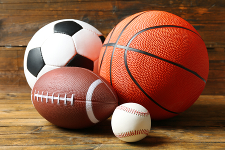 Foto de Sports balls on wooden background - Imagen libre de derechos