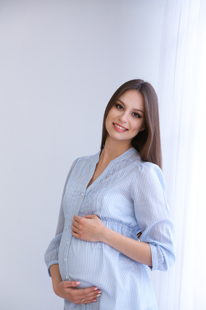 Pregnant woman on white wall background, indoors