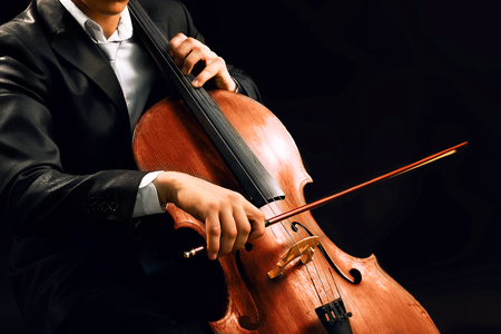 Photo pour Man playing on cello on dark background - image libre de droit