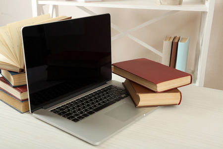 Laptop with books on table close up