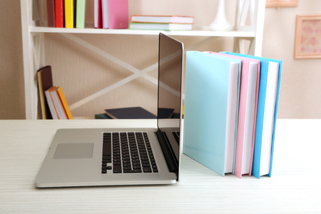 Stack of books with laptop on table in room
