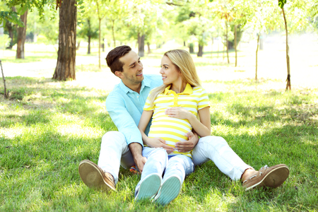 Young pregnant woman with husband sitting on green grass in park