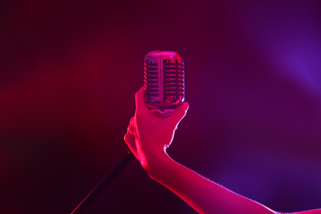 Female hand holding a retro microphone against colourful background