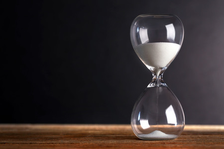Photo pour Hourglass on wooden table on grey background - image libre de droit