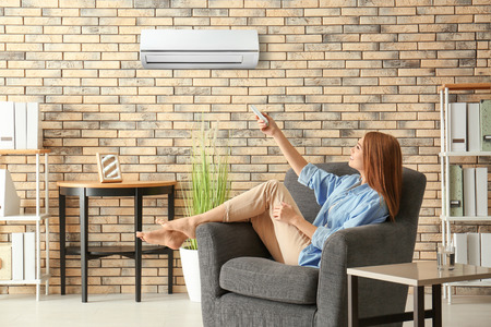 Foto de Young woman switching on air conditioner while sitting in armchair at home - Imagen libre de derechos