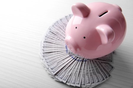 Pig moneybox and dollar banknotes on wooden background