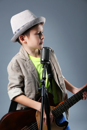 Little boy playing guitar and singing with microphone on grey backgroundの写真素材