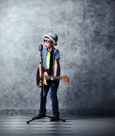 Little boy playing guitar and singing with microphone on a grey wall backgroundの写真素材