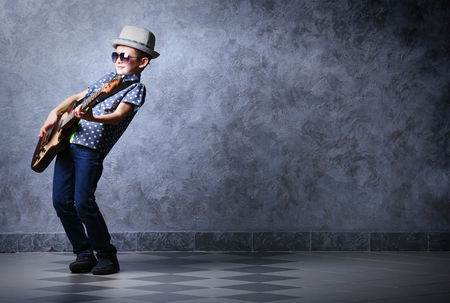 Foto de Little boy playing guitar on a grey wall background - Imagen libre de derechos