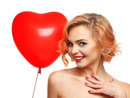 Playful attractive blond girl holding red heart balloon, isolated on white