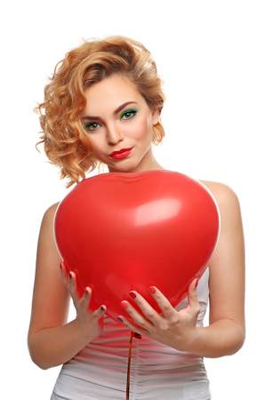 Attractive blond girl holding red heart balloon, isolated on white