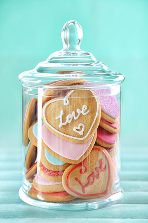 Foto de Assortment of love cookies in jar on blue background - Imagen libre de derechos
