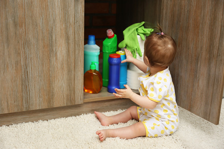 Photo pour Little girl playing with detergents in kitchen - image libre de droit