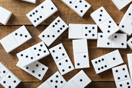 Heap of dominoes on wooden table