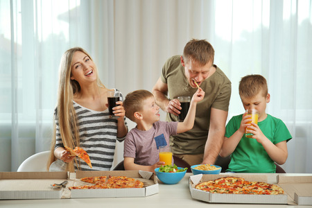 Photo pour Happy lovely family eating pizza - image libre de droit
