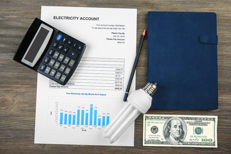 Photo for The concept of saving money. Calculator, bulb and electricity bill - Royalty Free Image