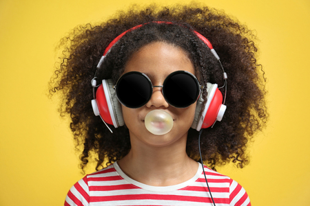 Photo pour Afro-American little girl with headphones and sunglasses chewing gum on yellow background - image libre de droit