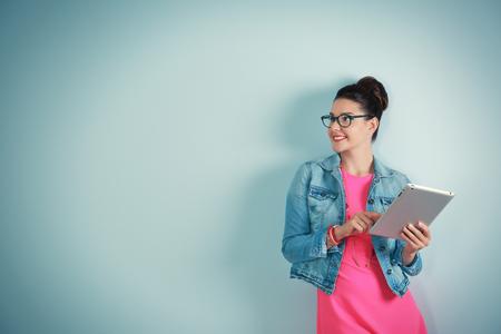 Foto de Cute young woman holding tablet on light background - Imagen libre de derechos