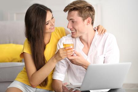 Photo pour Beautiful couple surfing internet on laptop at home - image libre de droit
