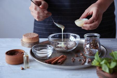 Photo pour Woman making coffee body scrub on wooden table - image libre de droit