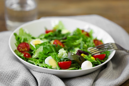 Plate of fresh delicious salad on napkin, closeup